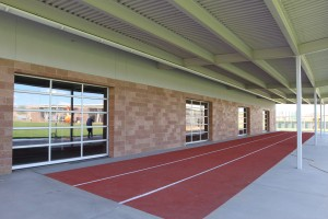 Outside the training building is a spongy track. The weight room has large pull-open doors that open to the outside.