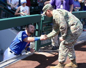 Kyle Schwarber shakes the hand of a serviceman